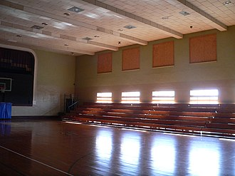 Hartington City Hall and Auditorium - Interior of auditorium looking southeast. The proscenium arch is visible at the east end of the auditorium, behind the basketball hoop. In recent years, the upper band of windows specified by William L. Steele has been filled in.
