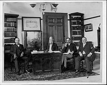 four men and desk