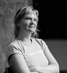 "A black and white photograph of a blond woman looking up with arm cross about her ""I Love To Share"" shirt"