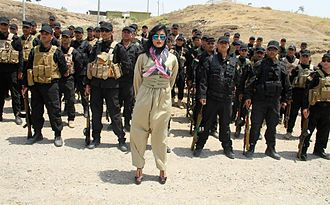 Helly Luv - Kurdish pop star Helly Luv poses in front of Kurdish Peshmerga troops at a base in Dohuk on July 5, 2014