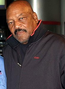 Jim Brown, wearing a jacket, poses for a picture.