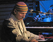 A man behind a microphone, with one of his hands on a black and white keyboard, wearing a dress shirt and a multi-colored cap.