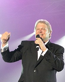 Upper body shot of a 61-year old man who is smiling and holding a microphone to his mouth in his left hand. His eyes are partly closed and  his right arm is raised to shoulder height with his fist clenched. He is wearing a dark coat and white shirt with his hair cut short.