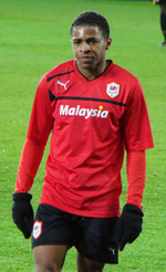 A man with short dark hair wearing a red football jersey, black gloves and black shorts. He is standing on a grass pitch.