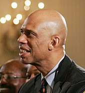 A bald black person, wearing a gray suit and a tie, looks to the left.