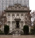 Photograph of the Leland Stanford House, an impressive Victorian with a modern office tower rising behind.