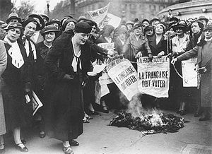 "First-wave feminism - Louise Weiss along with other Parisian suffragettes in 1935. The newspaper headline reads, in translation, ""THE FRENCHWOMAN MUST VOTE""."