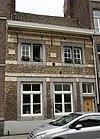 foto van Huis met mergelstenen kroonlijst, boven vlakke mergelblokken.