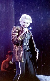 Madonna wearing a majenta jacket and black pants singing to a microphone held in her right hand