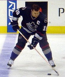 An ice hockey player stickhandling the puck. His head is down and his skates are shoulder-width apart. Wearing a black jersey, he is helmetless.