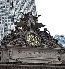 A large clock and stone sculptural group adorning the building's facade