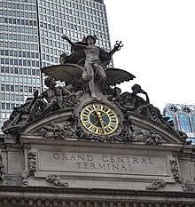 Un grande orologio e un gruppo scultoreo in pietra che adornano la facciata dell'edificio