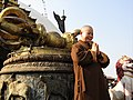Monk taking picture in front of vajra at Swayambhu.jpg