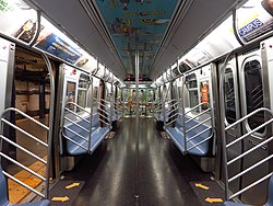 The interior of R160 car 9160, with artwork on the ceiling and at the ends of the car, as well as spreaded-out arrow decals inside the car's doorways