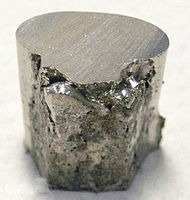 A pitted and lumpy piece of nickel, with the top surface cut flat