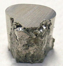 A pitted and lumpy piece of silvery metal, with the top surface cut flat