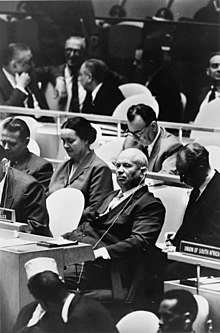 En eldre mann sitter blant FNs delegasjonsbord og ser på kameraet.