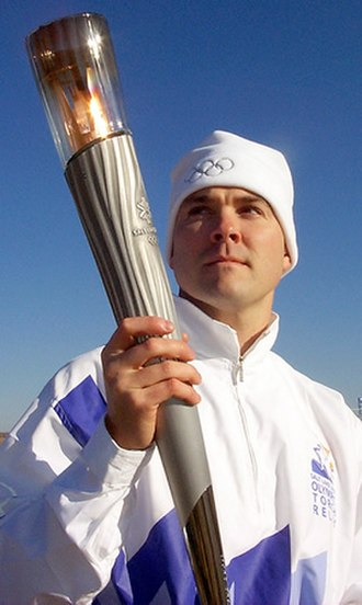 2002 Winter Olympics torch relay - Torchbearer in Olympic livery with 2002 Olympic Torch