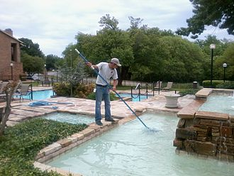 Swimming pool service technician - This swimming pool service technician is using a pool skimmer to remove debris from a courtyard fountain at an apartment complex in Tulsa, Oklahoma.