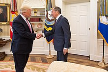 Two men in their 70s wearing suits and ties shaking hands, standing in the White House Oval Office