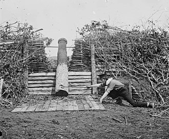 """Quaker gun - Quaker gun near Centreville, Virginia, in March 1862, after the Confederate withdrawal; a man with a stick is pretending to """"fire"""" it with a linstock"""