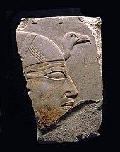 Fragment van een prachtig geschilderd reliëf met het hoofd van een vrouw met een hoofdtooi