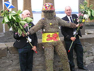 South Queensferry - The Burry Man takes a rest supported by his two attendants.