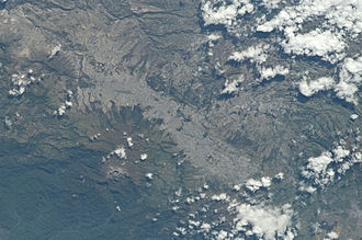 Quito - View of Quito from the International Space Station (north is at the left of the image). Quito sits on the eastern slopes of the Pichincha Volcano, whose crater is visible.