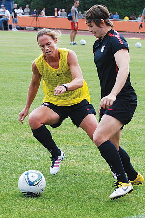 Christie Pearce - Pearce (in yellow) vies for the ball with U.S. teammate Amy LePeilbet during practice June 30, 2011, in Heidelberg, Germany.