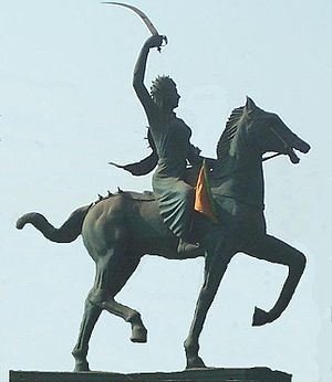 Statue of a horse ridden by a woman holding a sword