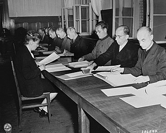 SS Race and Settlement Main Office - Some of the 14 defendants in the RuSHA Trial at Nuremberg read the indictments against them in July 1947.