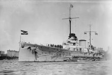 A large warship sits in harbor, with two smaller boats alongside. High-rise buildings are seen in the distance.