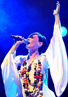 A 34-year-old woman is shown in left profile, she is singing into a microphone in her right hand, with her head titled back and looking forward. Her left arm is raised in a white robe with wide sleeves. She wears a multi-stranded necklace with numerous beads of various sizes and colours.