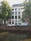 foto van Hoog herenhuis met lage bovenverdieping en eenvoudige gepleisterde lijstgevel. De deur heeft een gesneden omlijsting met touwornament en een gesneden kalf