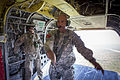 Sgt. 1st Class Garrett Williams signals paratroopers aboard a CH47 Chinook helicopter to stand up to prepare to jump in 2013.jpg