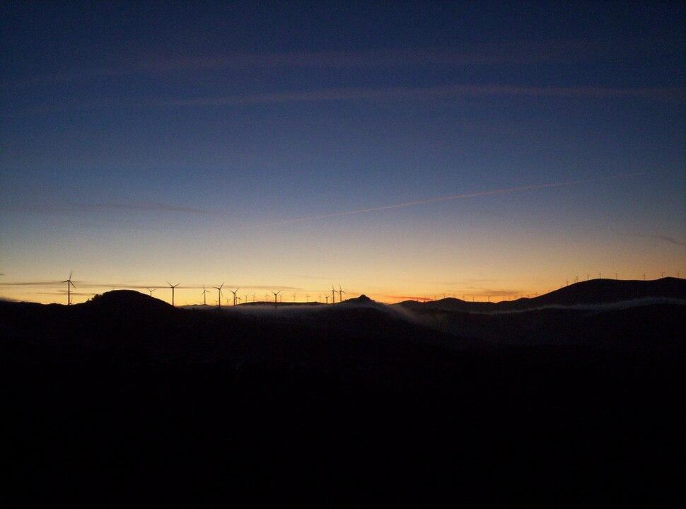 Solpor e parque eólico no horizonte.