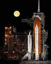 Space Shuttle Discovery under a full moon, 03-11-09
