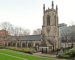 A substantial stone church seen from the northwest.  The tower has crocketted pinnacles, and the north wall of the body of the church has a series of large rectangular windows