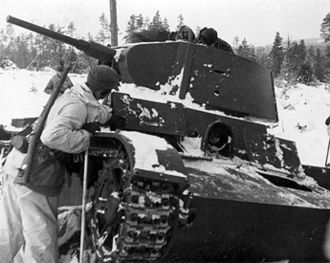 Swedish soldiers inspecting a destroyed Soviet tank