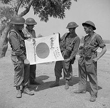 Photograph of four British soldiers examining s captured Japanese flag