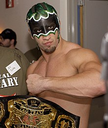 "A topless Caucasian man, with green hair and wearing a black and white mask that covers the top half of his face, poses with his arm rasied across his chest and his hand in a fist. A wrestling championship with a black strap is visible in the foreground of the image, and is inscribed with ""WWE Tag Team Championship""."