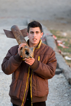 Palestinian rocket attacks on Israel - A boy carries a spent Qassam rocket in Sderot