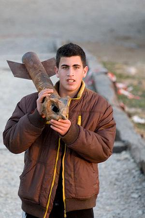 Palestinian rocket attacks on Israel - A boy carries a spent Qassam rocket in Sderot