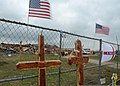 Two wooden crosses adorned with British flag pins and handwritten messages stand against a fence at Plaza Towers Elementary School in Moore, Okla., May 26, 2013 130526-Z-TK779-076.jpg
