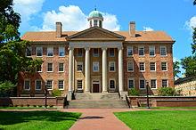 Um grande edifício com muitas janelas e quatro colunas na frente.