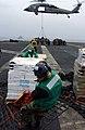 US Navy 050312-N-5821P-043 Storekeeper Seaman Joe Rinn of Houston, Texas, maneuvers supplies across the flight deck aboard the conventionally powered aircraft carrier USS Kitty Hawk (CV 63).jpg