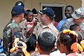 US Navy 070926-N-7088A-324 Mission commander Capt. Bob Kapcio, attached to Military Sealift Command hospital ship USNS Comfort (T-AH 20), gives a pencil to a student at the Grove Primary School.jpg