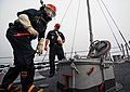 US Navy 080819-N-0807W-146 A Sailor wearing a self-contained breathing apparatus prepares to open a scuttle.jpg