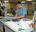 US Navy 090416-A-3007S-001 Spc. Timothy Warren, assigned to the 807th Medical Command (Deployment Support), holds the hand of a Haitian girl in the post-anesthesia care unit aboard the Military Sealift Command hospital ship USN.jpg