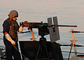 US Navy 090824-N-1522S-017 Gunner's Mate 1st Class Matthew Davis prepares to man a .50-caliber machine gun aboard the guided-missile destroyer USS Farragut (DDG 99).jpg